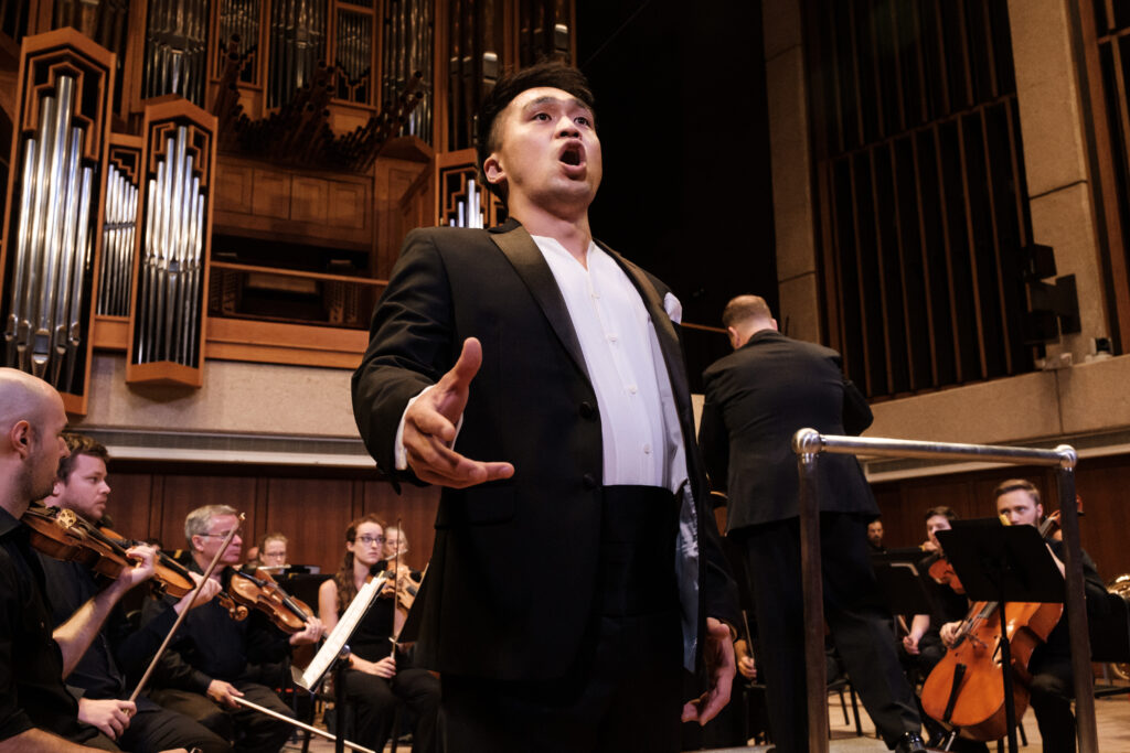 Performer stands in front of an orchestra while singing at concert