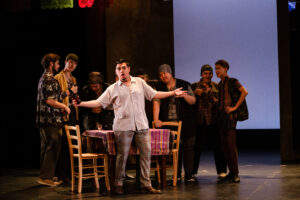 Masetto holds a beer and stands in front of a table with the chorus men surrounding