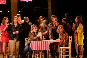 The chorus gathers around a table during a party