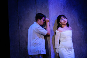 Masetto faces the wall while Zerlina stands with her back against the wall around a corner