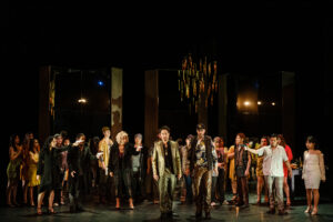 The company gathers behind Giovanni and Leporello as the principals point guns