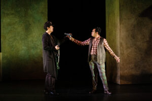 Masetto points a gun at Giovanni, who is holding a machine gun