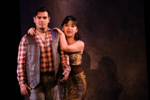 Zerlina drapes her arms around Masetto's shoulders
