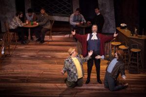 Falstaff, Pisola, and Bardolfo celebrate at the bar