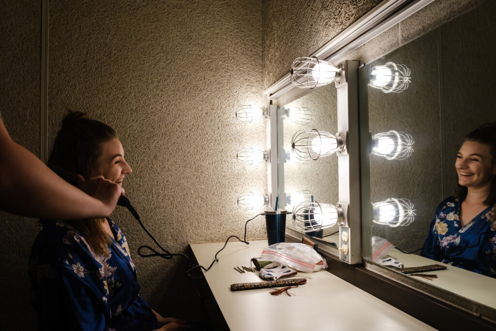 Performer sits at a dressing room table while her hair is done