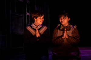 Miles and Flora share a creepy look while kneeling with prayerful hands