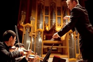 conductor leads the UT symphony orchestra