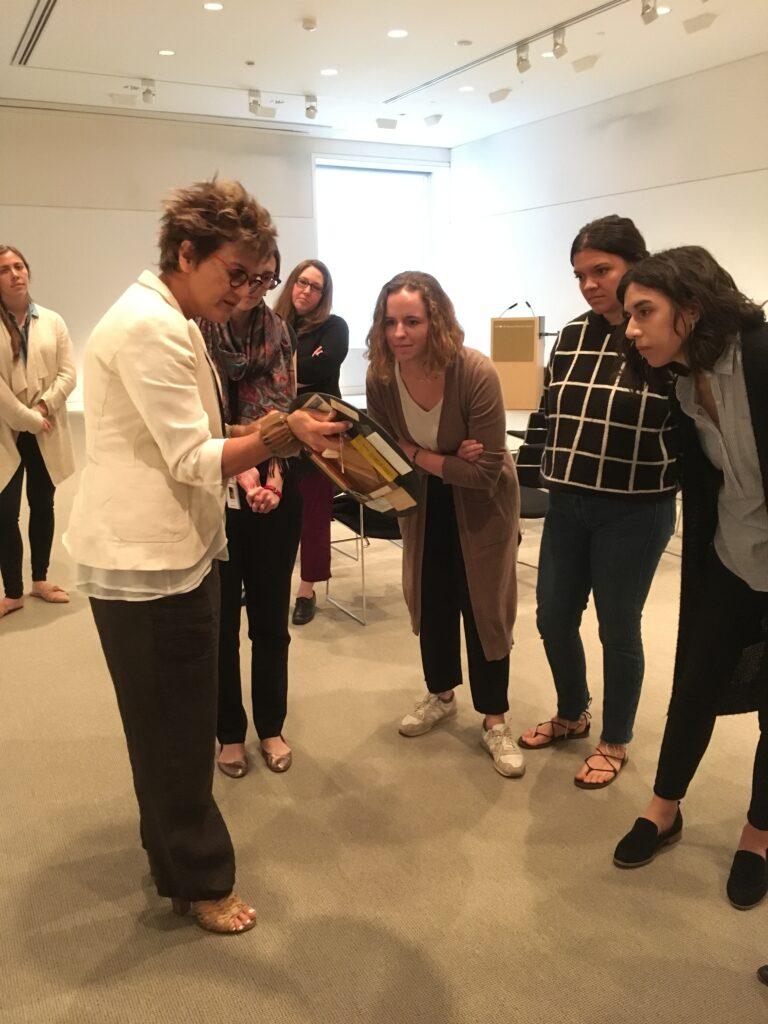CLAVIS examine a work of Brazilian abstract art curator Mari Carmen Ramirez holds in her hand