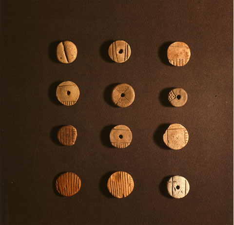 12 similarly shaped tokens with different markings