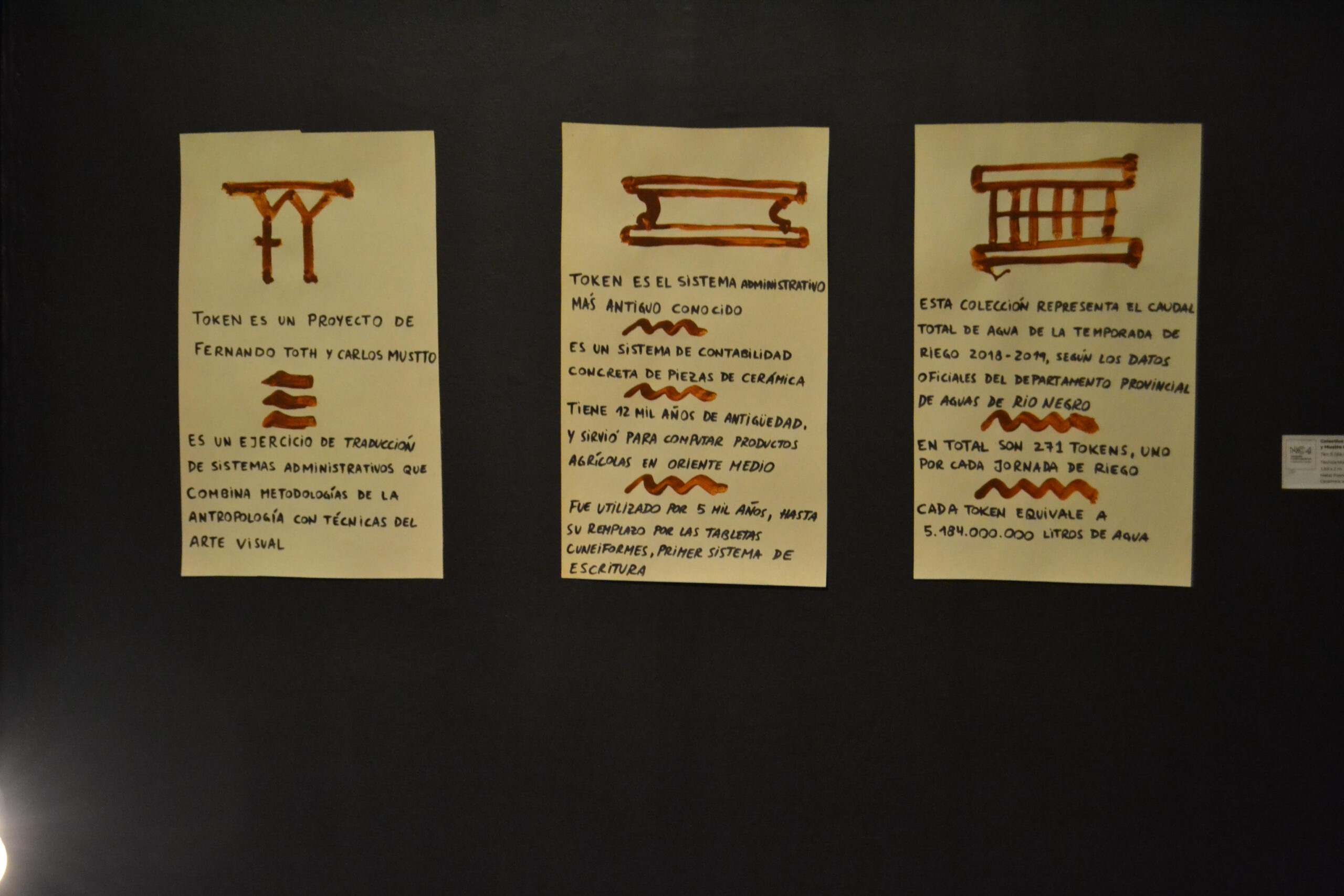 Three illustrations of symbols with text in spanish mounted on the wall in gallery
