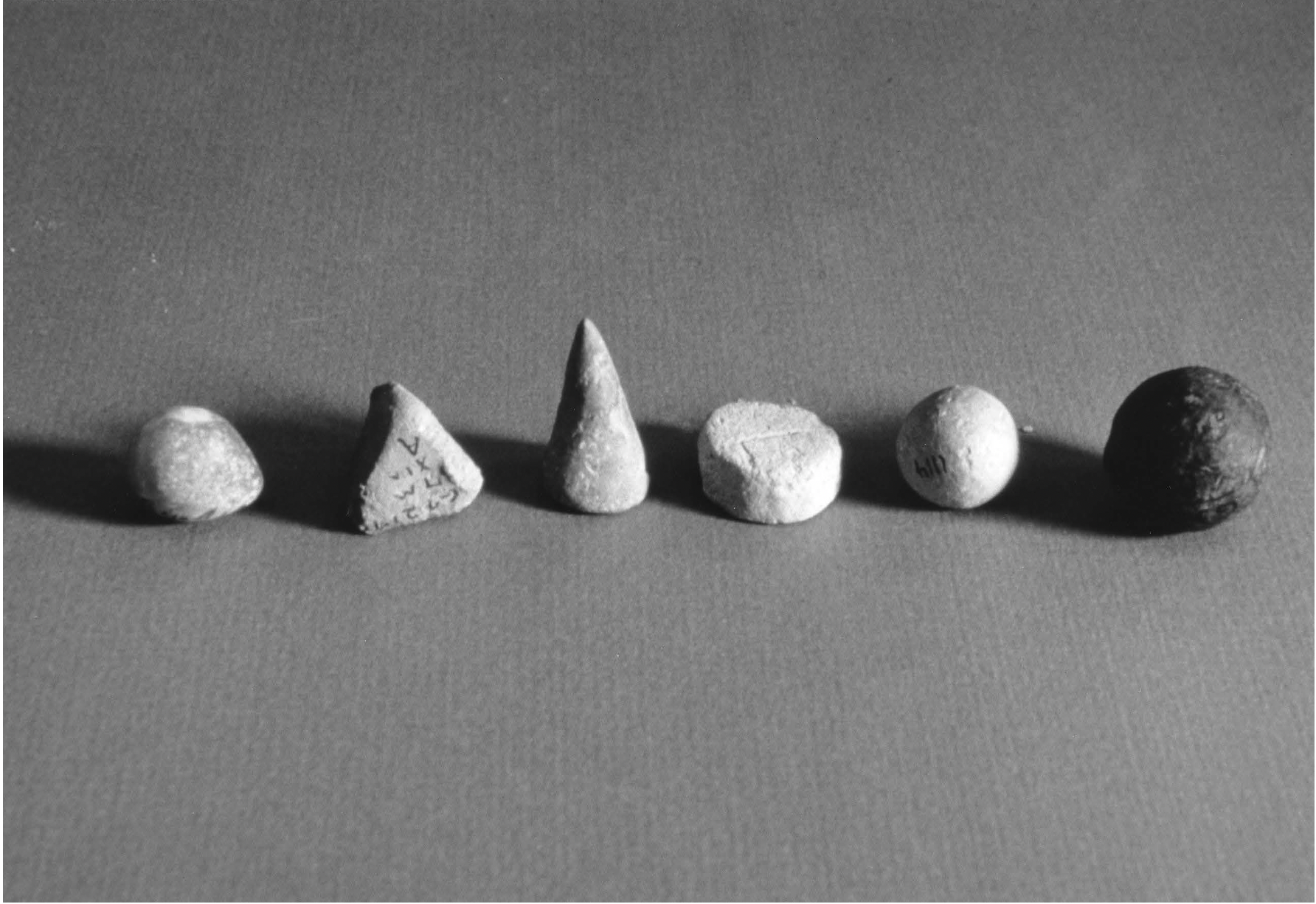 Photograph of 6 tokens in various shapes.