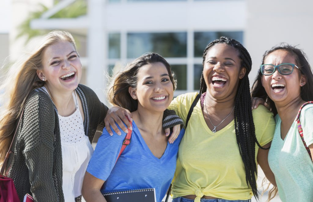 Four multi-ethnic teenage students on campus