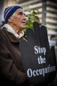 A man holds a sign calling for the end to Israeli occupation of Palestine. Photo Credit: Juliane Kravik Creative Commons Flickr