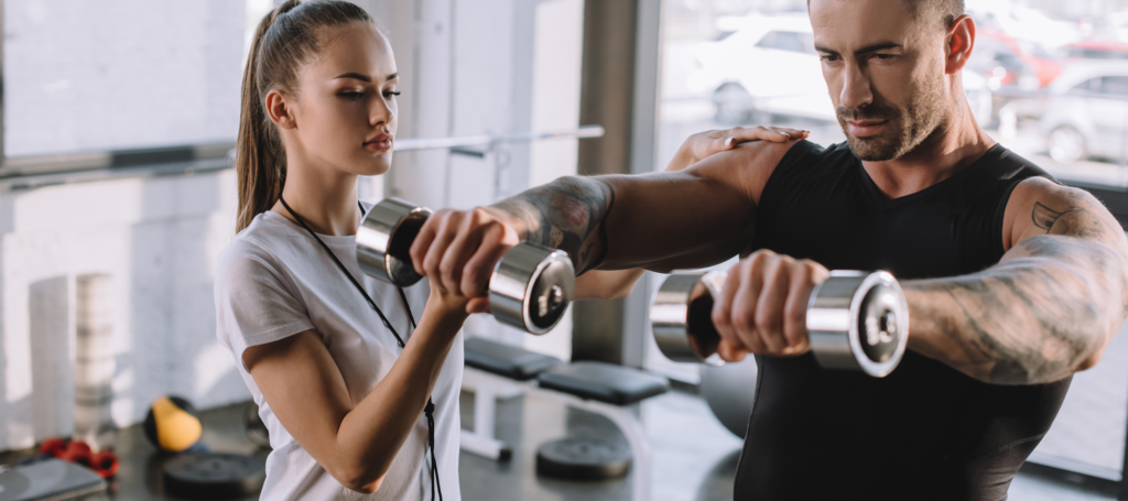 Young female fitness trainer working with a male client.