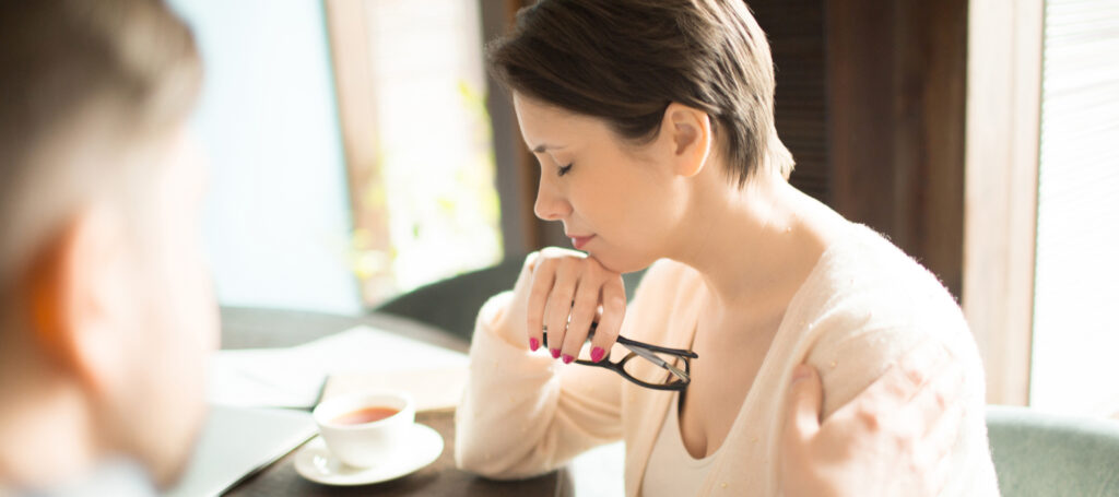 Exhausted woman holding glasses and keeping eyes closed while sitting near colleague at cafe table.