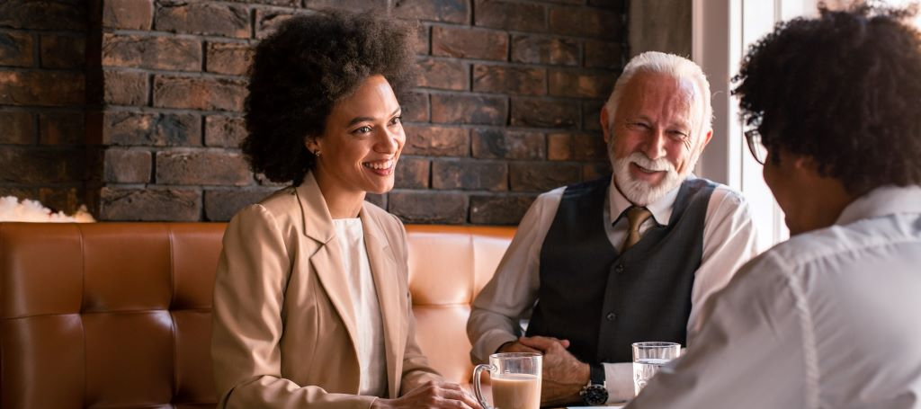A young BIPOC woman and young BIPOC man laugh over coffee with their older white coworker.