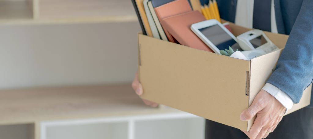 Laid off employee leaving office with items from desk packed into a cardboard box