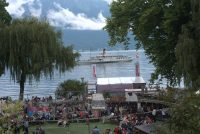 picture of steam boat on lake in distance and audience at Montreux in the foreground