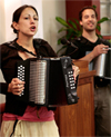 a young man and woman playing the accordian
