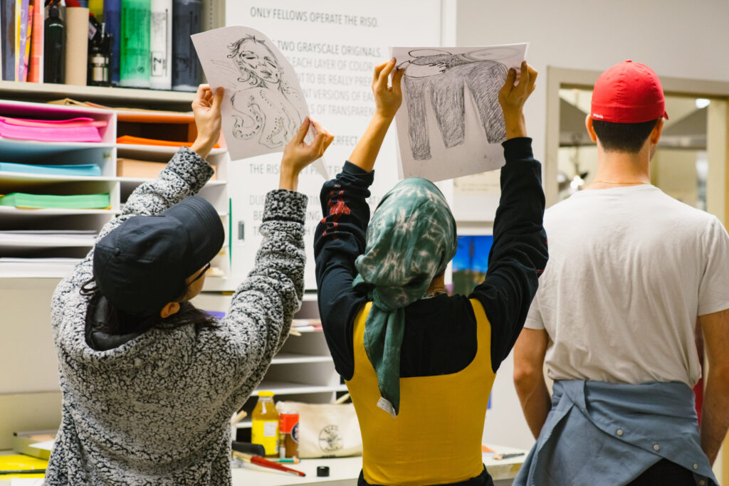 Students look at artworks in program together in the Print Lab.