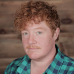 Headshot of redheaded non-binary actor and commedian Becca Blackwell wearing green and black plaid button down shirt