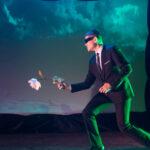 three actors on dark stage in futuristic costumes