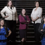 Members of the Texas House LGBTQ Caucus. Five people standing on dark and large staircase, some in blazers and slacks, others in blouses and skirts, hands on hips or arms crossed.