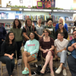 Group photo of transgender feminisms reading group members. Some people are standing, some are sitting, one is holding a cane.