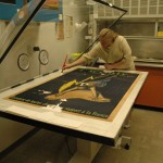 School of Information student Laura Bedford washes the poster on the vacuum-suction table.