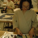 Volunteer Nani Lew cuts and prepares strips of Japanese paper for attachment to the poster.