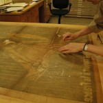 Head of Paper Conservation Stephanie Watkins aligns the poster before attaching the backing paper.
