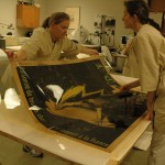 Bedford and Watkins brush out the poster onto the Japanese backing paper while the poster is attached to a sheet of Mylar.