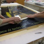 Once the poster has been aligned, Watkins and Bedford remove the Mylar cover.