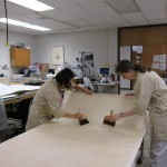 Lew and Watkins place a large sheet of Japanese paper on the table before it is applied to the poster.