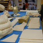 Stacks of creased board and cloth pieces ready to be sewn, a pile of completed padded cloth covers. Head of the preservation lab Apryl Voskamp, and work-study student Liz Phan consult. Photo by Mary Baughman.