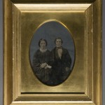 Seated Couple. Unidentified photographer. Oil on tintype. Ca. 1850s. Federal Revival style gilt frame.