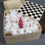 This chess set was owned by Ezra Pound and was acquired as part of the Marcella Spann Booth collection. The individual chess pieces are wrapped in tissue paper, and the board sits on top of an acid-free mat board grid. The original box for the set is pictured under the board. Photo by Pete Smith.
