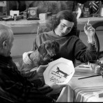 While Jacqueline Roque and Lump, David Douglas Duncan's dachshund, look on, Pablo Picasso inspects the souvenir luncheon plate he has just painted for and dedicated to Lump. La Californie, Cannes. Gelatin silver negative. April 19th, 1957. © David Douglas Duncan.