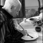 Upon learning that Lump, David Douglas Duncan's dachshund, had never had a plate of his own, Pablo Picasso took the luncheon plate in front of him and began painting the dog's portrait on it. La Californie, Cannes. Gelatin silver negative. April 19th, 1957. © David Douglas Duncan.