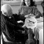 While Jacqueline Roque looks on, Lump, David Douglas Duncan's dachshund, inspects the luncheon plate Pablo Picasso has just painted for and dedicated to him. La Californie, Cannes. Gelatin silver negative. April 19th, 1957. © David Douglas Duncan.