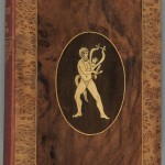 "Edward Bulwer-Lytton's ""The Last Days of Pompeii"" (London: Collins, ca. 1910s). The Library of Edward Alexander Parsons. Polished wooden inlaid boards cover this otherwise unassuming edition of Lytton's popular novel, leaving the original spine visible. The inlaid upper cover is composed of at least eight separate pieces of wood, cut and fitted together so precisely that the surface feels completely smooth to the touch. Inlaid bindings peaked in popularity in the seventeenth and eighteenth centuries, so this early twentieth-century repackaging was likely a deliberately anachronistic choice—perhaps a playful reference to the famous mosaics of Pompeii. Photo by Pete Smith."