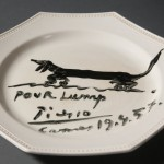 Souvenir luncheon plate painted by Pablo Picasso and dedicated to Lump, David Douglas Duncan's dachshund. Black glaze on commercial ceramic plate. 24 cm. in diameter. April 19th, 1957. Photo by Pete Smith. Image courtesy of Harry Ransom Center.