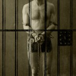 Photo of Houdini in chains in a jail cell. Undated and unidentified photographer.
