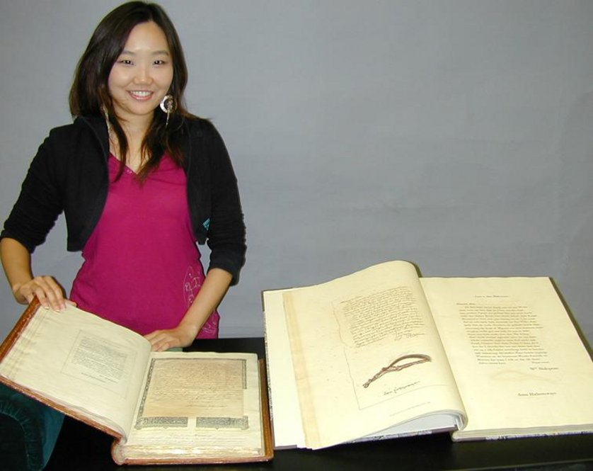"Inkyung Youm, a graduate intern in the Ransom Center's Conservation Department, with the printed and facsimile versions of William Henry Ireland's handiwork, ""Miscellaneous Papers and Legal Instruments under the Hand and Seal of William Shakespeare"" and ""Fabricated Shakespearian Manuscripts."""