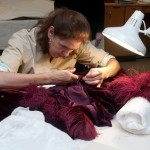 Cara Varnell, independent art conservator, repairs the burgundy ball gown. Photo by Pete Smith.