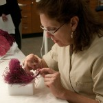 Varnell mends an original feather that broke at the point where it was stitched to the gown. Photo by Pete Smith.