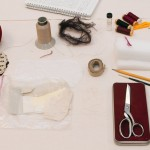 Varnell's materials, including adhesive, threads, notebook, and the needle case made for her mother at age five. Photo by Pete Smith.