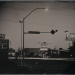 """Robb Kendrick. """"Untitled: Elko, Nevada series for National Geographic Magazine,"""" July 2003. """"This image was taken in 2003 in Elko Nevada for National Geographic. This was a small story about the town. It was the first time NG had ever commissioned a tintype as the process was obsolete by the time they started publishing images in 1887. The street scene taken at dusk showing the motel and casino signs, street light and car headlights was an image I attempted to show the Night Life in this gambling town. Tintype exposures are very long to begin with, at dusk they are painfully long. In the end I made three plates and the two that were successful were made with 14 minute exposure times which was far longer than any exposure I had ever heard from historic or contemporary tintype photographers. Also, I had never seen an image made after the sun went down."""""""