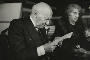 Undated photo of Isaac Bashevis Singer, with wife Alma in the background. Unidentified photographer.