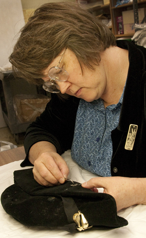 Mary Baughman uses tweezers to remove moth cocoons from a hat that is part of the Sir Donald Wolfit collection. The hat was used in productions of Shakespeare's plays in England, between 1937-1967. Photo by Pete Smith.